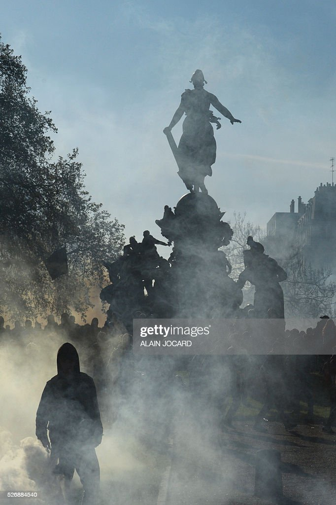 People surrounded by smoke are gathered on the Place de la Republiques during clashes between French anti riot police and protesters during a clash during the traditional May Day demonstration in Paris on May 1, 2016.