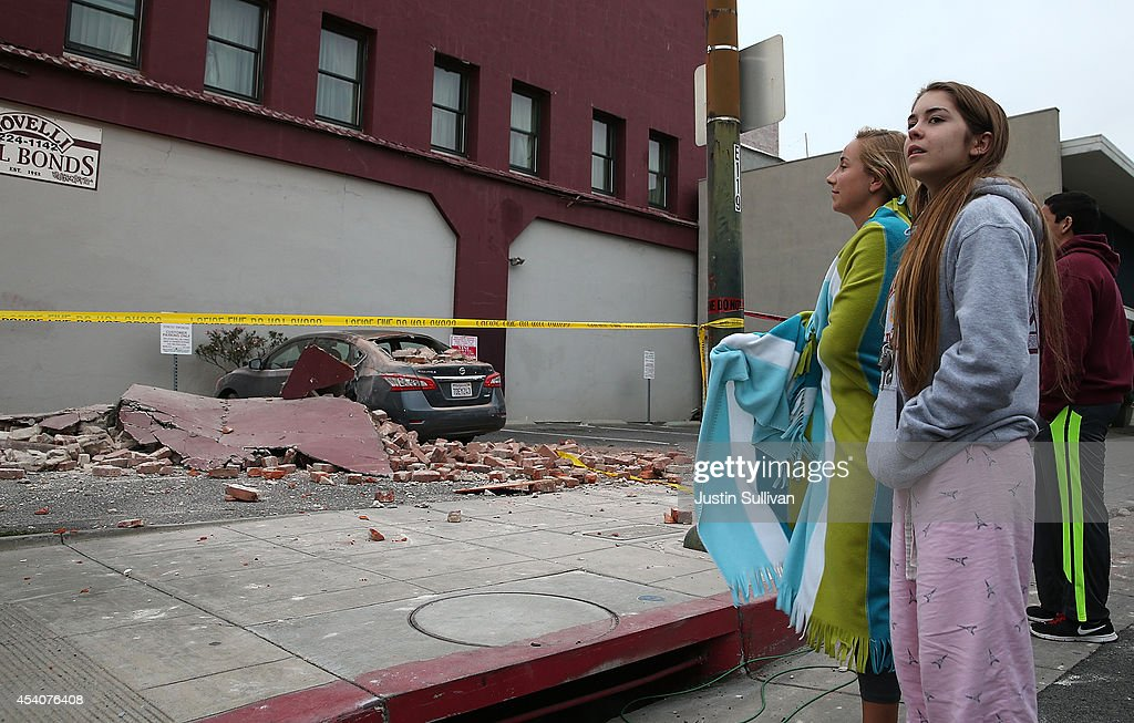 People survey a damaged car following a reported 6.0 earthquake on August 24, 2014 in Napa, California. A 6.0 earthquake rocked the San Francisco Bay Area shortly after 3:00 am on Sunday morning causing damage to buildings and sending at least 70 people to a hospital with non-life threatening injuries.