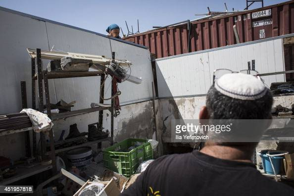 People survey damage to a house made by a rocket that hit from Gaza Strip on July 10 2014 in Netivot Israel Due to the recent escalation in the...