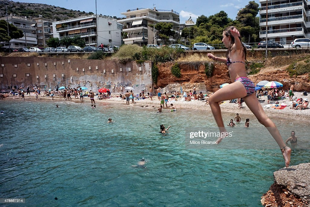 People swim and jump in the water at the beach on June 28 2015 in Athens Greece Greece is anxiously awaiting a decision by the European Central Bank...