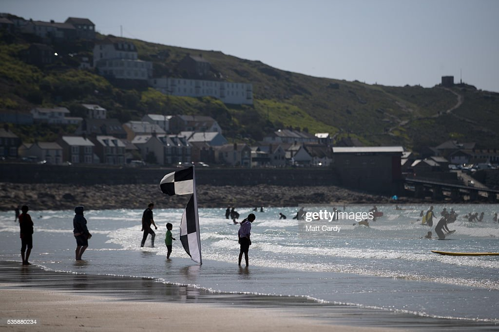 People swim and surf in the sea as they enjoy the fine weather at Sennen Cove on May 30, 2016 in Cornwall, England. As some parts of the UK were bathed in sunshine for the bank holiday weather forecasters have warned that gale-force winds and thunderstorms will sweep in from the east overnight.