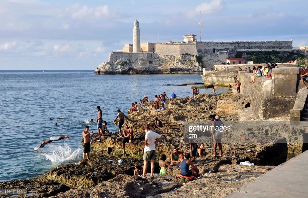 People swim by the reef close to the Malecon wall in Old Havana, Cuba, on August 25, 2010.