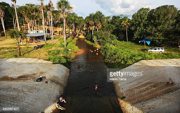 People swim in a deforested section beneath the Interoceanic Highway in the Amazon lowlands on November 16 2013 in Madre de Dios region Peru The...
