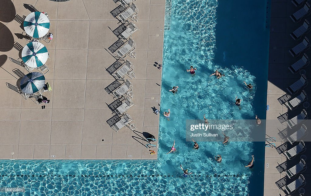 People swim in a pool at a housing development on March 6, 2013 in Mesa, Arizona. In 2008, Phoenix, Arizona was at the forefront of the U.S. housing crisis with home prices falling 55 percent between 2005 and 2011 leaving many developers to abandon development projects. Phoenix is now undergoing a housing boom as sale prices have surged 22.9 percent, the highest price increase in the nation, and homebuilders are scrambling to buy up land.