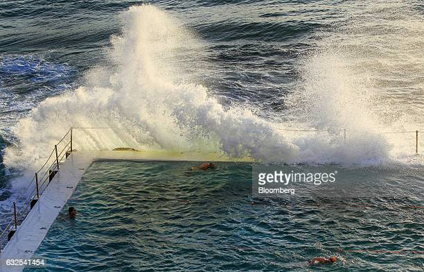 People swim in a pool at the Bondi Icebergs Swimming Club as a wave crashes against it at Bondi Beach in Sydney Australia on Monday Jan 23 2017...