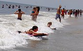 People swim in in the surf at Rockaway Beach on July 26 2016 in New York City A heat wave continues with temperatures expected to stay in the 90's...