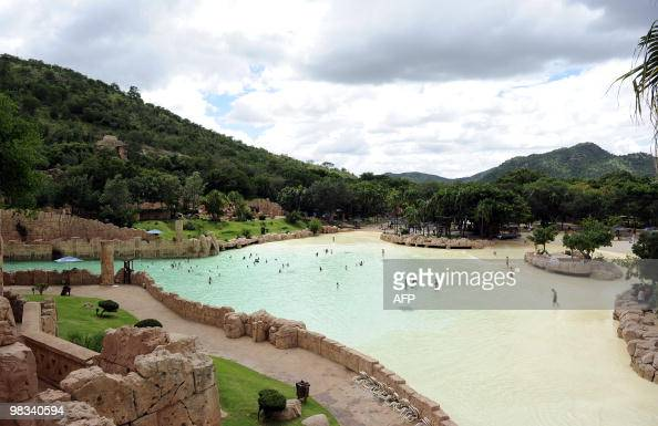 People swim in the artificial sandy beach of the Lost City water park in Sun City on February 22 2010 The shaking walkway leading to a manmade sandy...