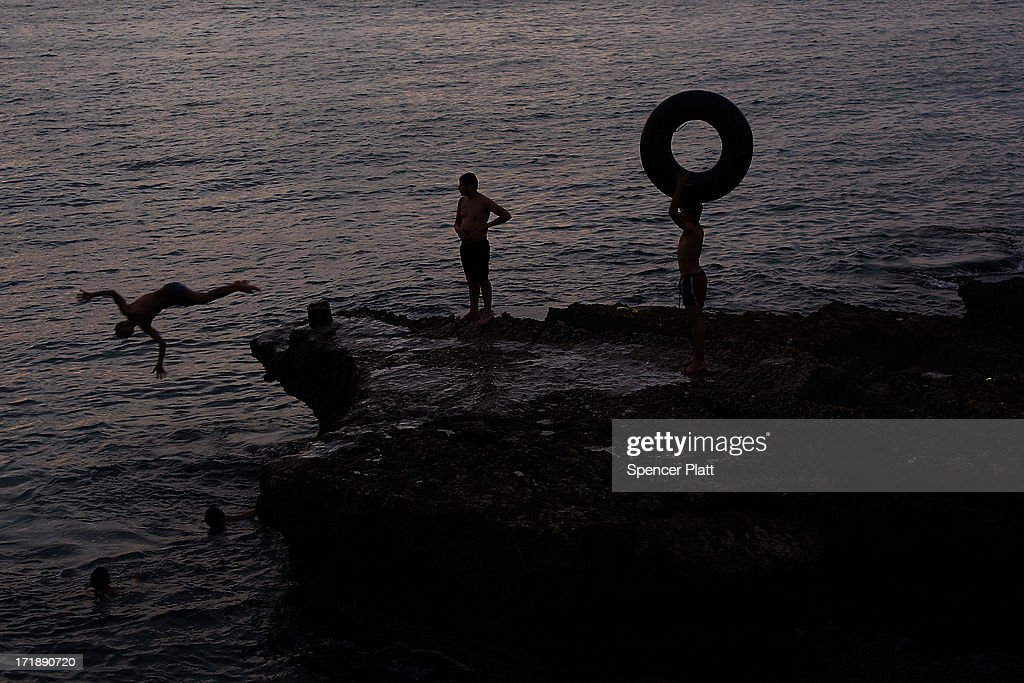 People swim in the Mediterranean on June 29, 2013 in Beirut, Lebanon. Currently the Lebanese government officially hosts 546,000 Syrians with an estimated additional 500,000 who have not registered with the United Nations. Lebanon, a country of only 4 million people, is now home to the largest number of Syrian refugees who have fled the conflict. The situation is beginning to put a huge social and political strains on Lebanon as there is currently no end in sight to the war in Syria.