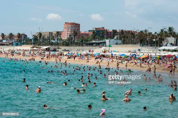 People swim in the sea and sunbathe on Mar Bella beach in the Catalonian coastal city of Barcelona on August 6 2017 / AFP PHOTO / Josep LAGO