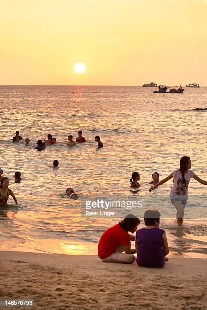 People swimming at sunset at Duong Dong beach.