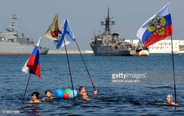 People swimming in the cold waters of the harbour of Sevastopol hold Russian national and navy flags to mark their support for Russian forces as a...