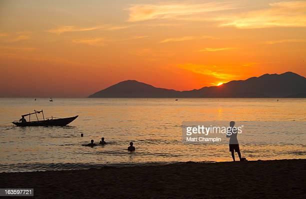 People Swimming on Vietnam Beach at Sunrise
