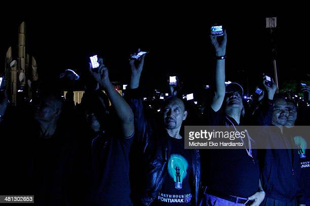 People switch on their phone light for a minute during a blackout as part of Earth hour celebration on March 29 2014 in Pontianak Indonesia Millions...