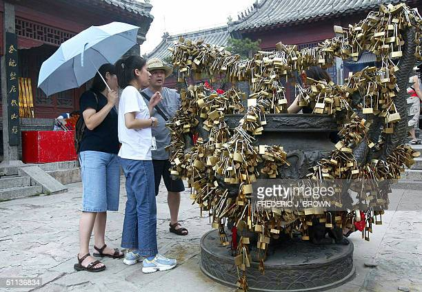 People take a closer look at a dragon cauldron filled with locks left by visitors in a traditional rite to bond relationships or offer blessings for...