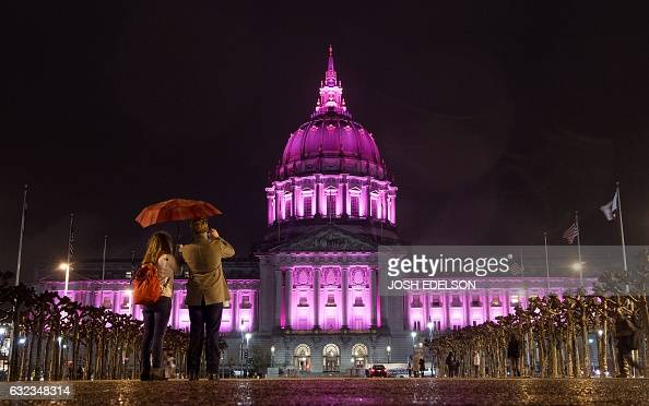 TOPSHOT People take a photo as City Hall is bathed lighted in pink after thousands of people marched to protest President Donald Trump and to show...