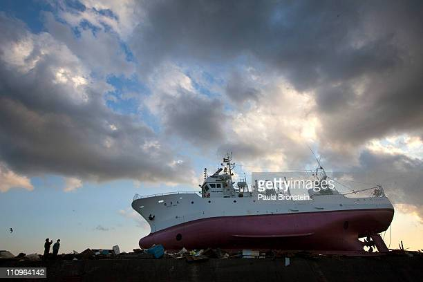 People take a photo of a ship sits on top of a tsunami wall at the port March 28 2011 in Ishinomaki Miyagi Japan More than two weeks after the...