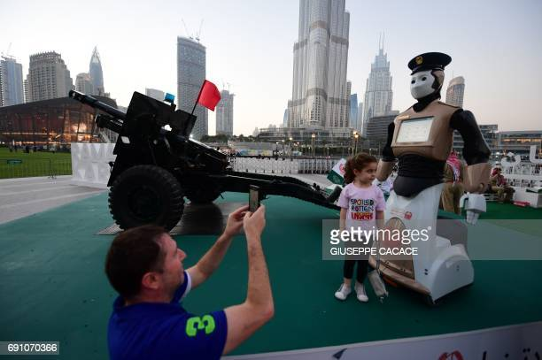 People take a picture with the world's first operational police robot near the Burj Khalifa in Downtown Dubai on May 31 as a military cannon is...