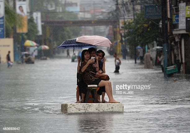 People take a selfie as they ride on a makeshift raft made of styrofoam after sudden heavy downpour inundated streets in the financial district of...