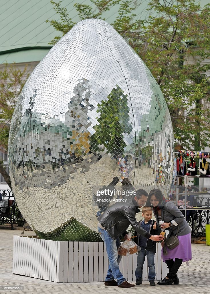 People take a selfie near a giant egg, named 'Diamond Easter Egg',3.5 m high, which is decorated with more than 15,000 mirror particles during the Ukrainian Easter hand made fair 'Easter country' at the Kiev-Pechersk Lavra in Kiev, Ukraine on April 30, 2016.