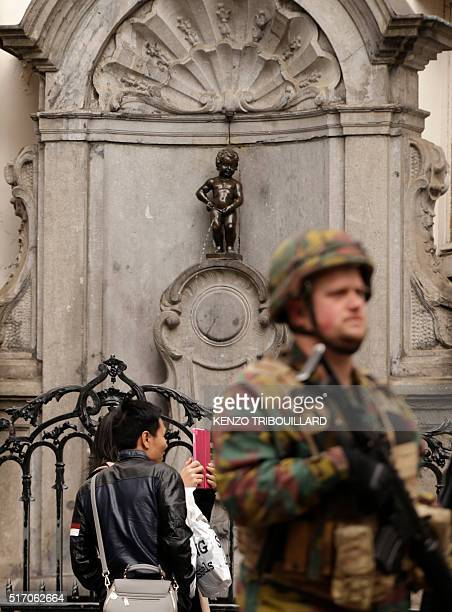 People take a selfie next to a soldier standing guard near the Manneken Pis in Brussels on March 23 a day after blasts hit the Belgian capital World...