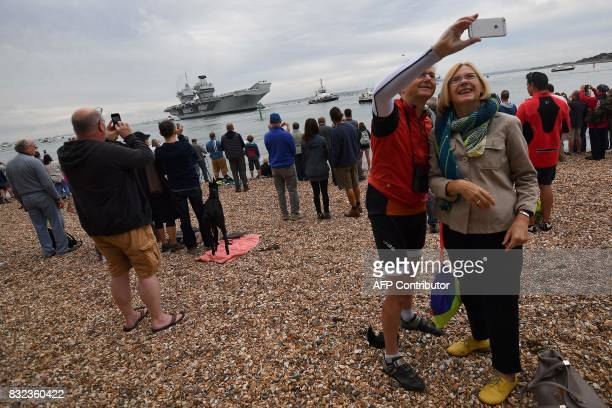 People take a 'selfie' photo as they line the shore to watch as tug boats manoeuvre the 65000tonne British aircraft carrier HMS Queen Elizabeth into...