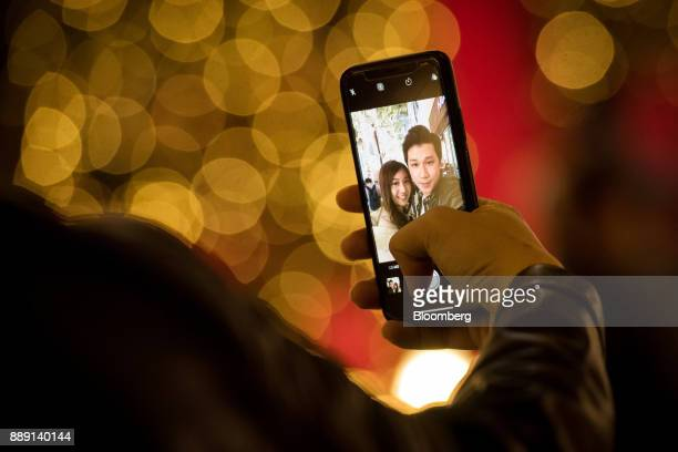 People take a selfie photograph with an Apple Inc iPhone in front of illuminated Christmas lights in Hong Kong China on Saturday Dec 9 2017 With more...