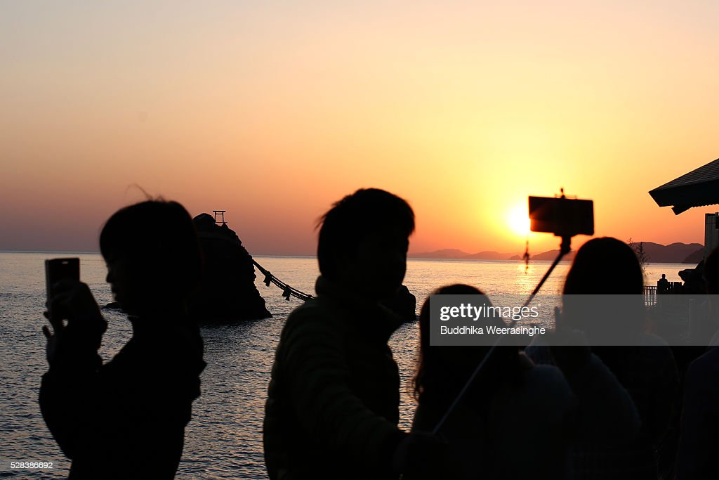 People take a selfie while sun rise between the 'Meoto-Iwa' or couple rocks and over the sea ahead of the Oshimenawahari ceremony at Futami Okitama Shrine on May 5, 2016 in Ise, Japan. The Oshimenawahari ceremony is held three times a year to exchange the 35 meters long heavy rope made of rice straw that connects the sacred Couple Rock - one small, one big. The Couple Rock serves as a gate to the Okitama Shrine, dedicated to the god Sarutahiko and goddess Ukanomitama from Japanese myth.