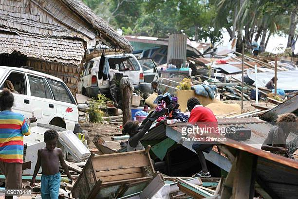 People take clothes from their collapsed houses two days after the 76 magnitude earthquake on April 4 2007 in Ghizo Island Solomon Islands