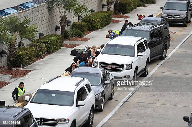 People take cover behind cars outside of Terminal 2 at Fort LauderdaleHollywood International airport after a shooting took place near the baggage...