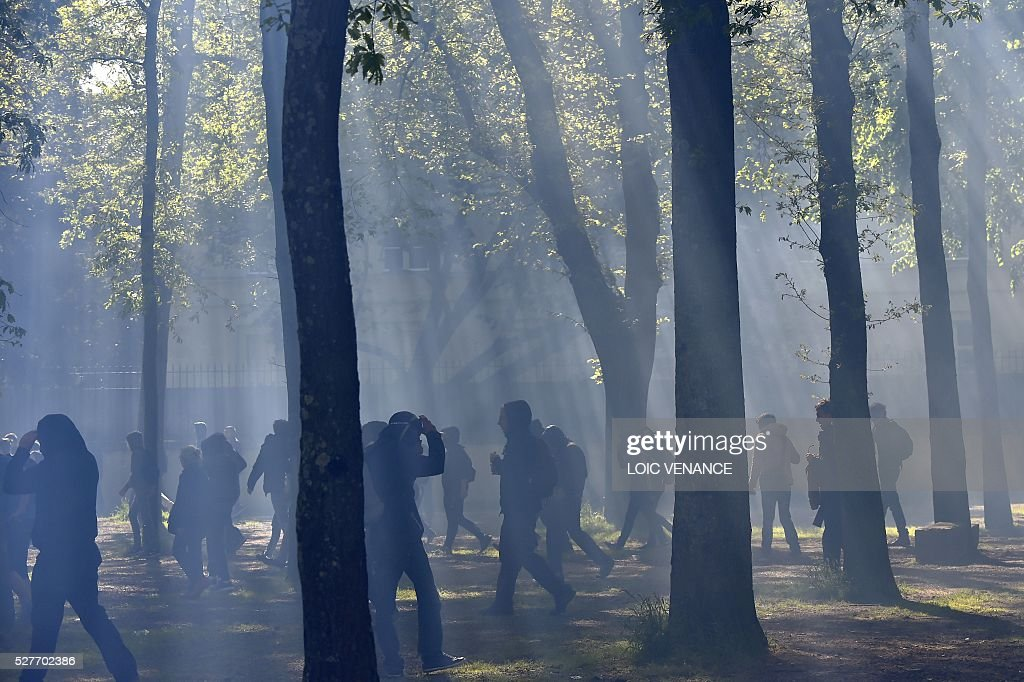 People take cover behind trees during a protest against the government's planned labour law reforms in Nantes, western France, on May 3, 2016. High school pupils and workers protested against deeply unpopular labour reforms that have divided the Socialist government and raised hackles in a country accustomed to iron-clad job security. / AFP / LOIC