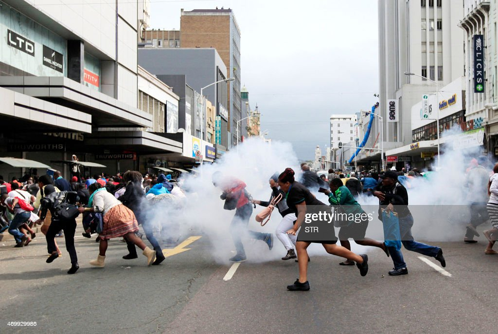 People take cover from a stun grenade and tear gas after a skirmish between locals and foreign nationals as thousands of people take part in the...
