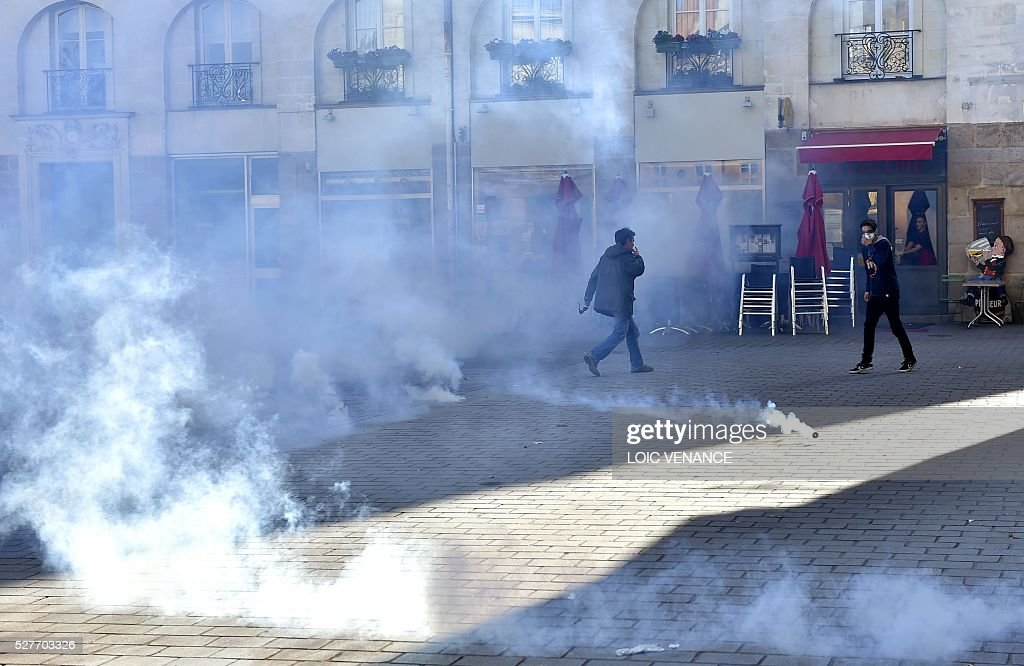 People take cover from tear gas fired by police during a protest against the government's planned labour law reforms in Nantes, western France, on May 3, 2016. High school pupils and workers protested against deeply unpopular labour reforms that have divided the Socialist government and raised hackles in a country accustomed to iron-clad job security. / AFP / LOIC