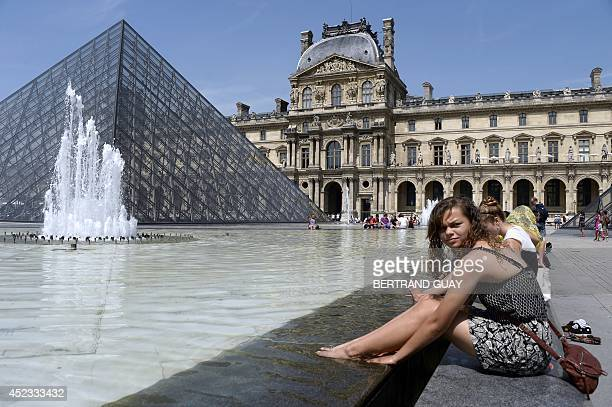 People take in the sun near a fountain in front of the Louvre Pyramid in Paris on July 18 2014 AFP PHOTO / BERTRAND GUAY