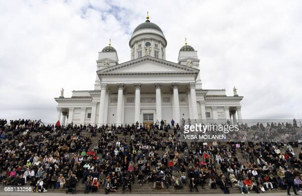 People take part at the state funeral ceremony of Finland's former President Mauno Koivisto outside the Cathedral in Helsinki on May 25 2017 / AFP...