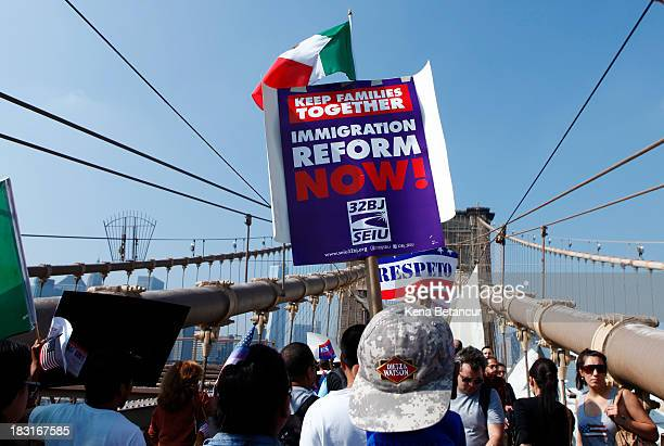 People take part during an immigration reform march across the Brooklyn bridge on October 5 2013 in New York City Immigration groups marched in 100...