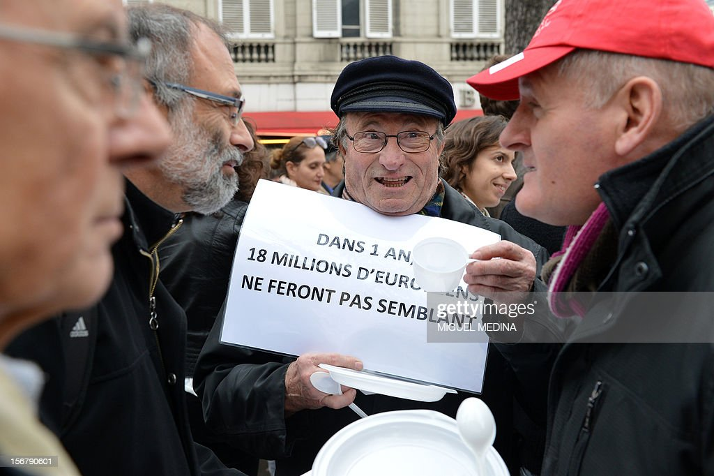 People take part in a 'Airfood' event, a giant air pic-nic without any food, organized by French association 'Secours Populaire' to ask for the renewal of a European food aid program on November 21, 2012 in front of the National Assembly in Paris. European heads of state will meet on November 22 and 23 and will take decisions on the European food aid. Papers read 'in 1 year, 18 millions european people will not pretend anymore'.