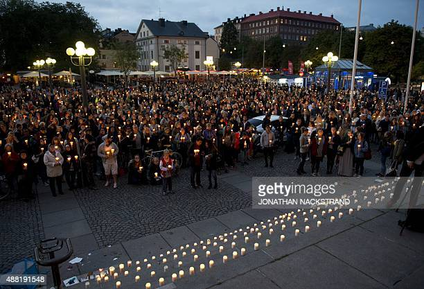 People take part in a candle light rally in solidarity with migrants seeking asylum in Europe after fleeing their home countries in Stockholm on...