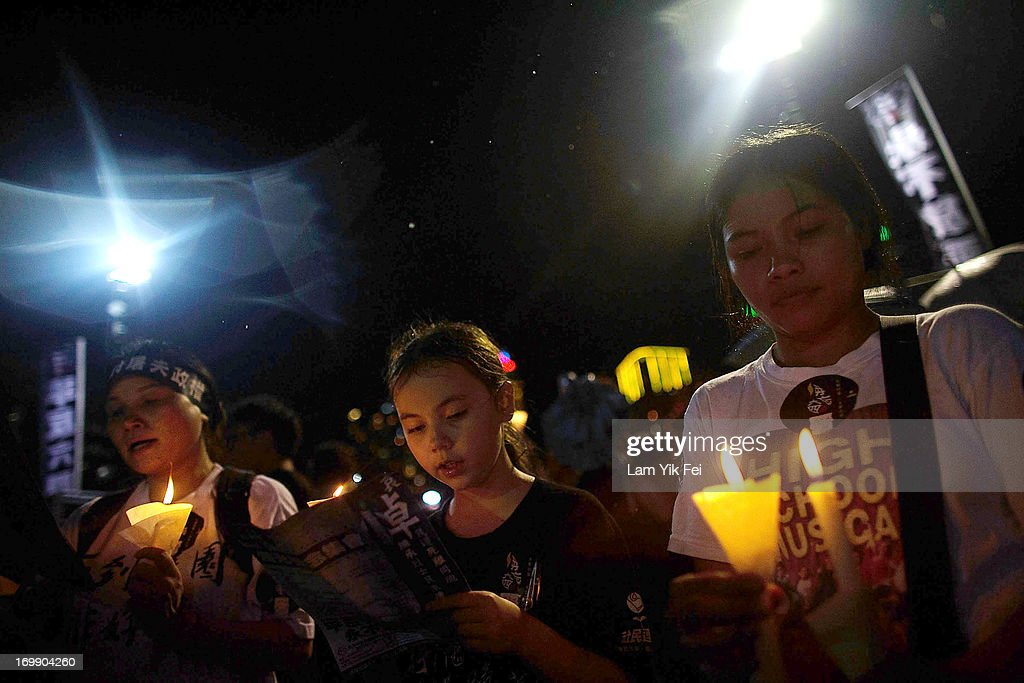 People take part in a candlelight vigil on the 24th anniversary of the Tiananmen Square protests during heavy rain on June 4, 2013 in Hong Kong, Hong Kong. Held to mark the crackdown on the pro-democracy movement in Beijing's Tiananmen Square on June 4, 1989.Pro-democracy groups hope to draw 150,000 people to the annual candlelight vigil in Hong Kong's Victoria Park, the only commemoration on Chinese soil.