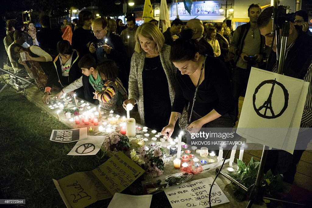 People take part in a candlelight vigil organised by the French cultural institute Alliance Francaise in the Cypriot port city of Limassol on November 15, 2015, in solidarity with the victims of coordinated attacks in Paris. Islamic State jihadists claimed a series of coordinated attacks by gunmen and suicide bombers in Paris that killed at least 129 people in scenes of carnage at a concert hall, restaurants and the national stadium.