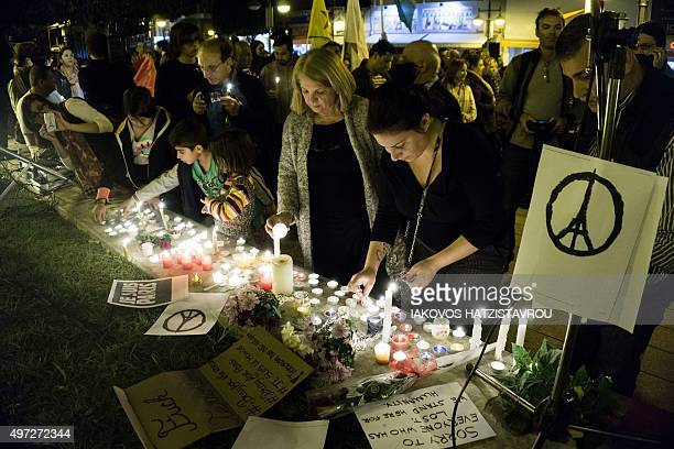 People take part in a candlelight vigil organised by the French cultural institute Alliance Francaise in the Cypriot port city of Limassol on...