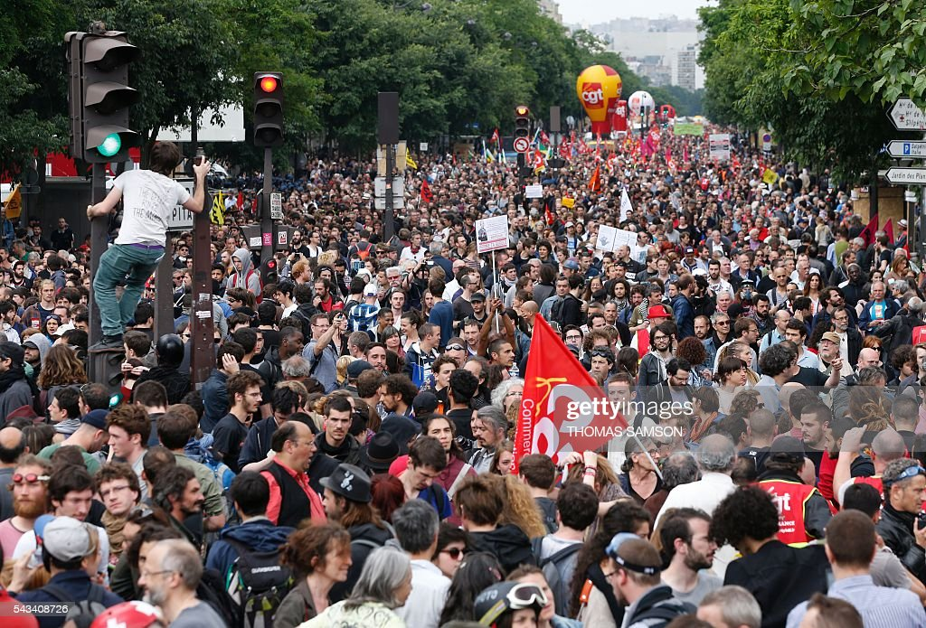 People take part in a demonstration against controversial labour reforms, on June 28, 2016 in Paris. Unions have called repeated strikes and marches in opposition to the law, which seeks to bring down France's intractable 10-percent unemployment rate by making it easier to hire and fire workers. / AFP / Thomas SAMSON