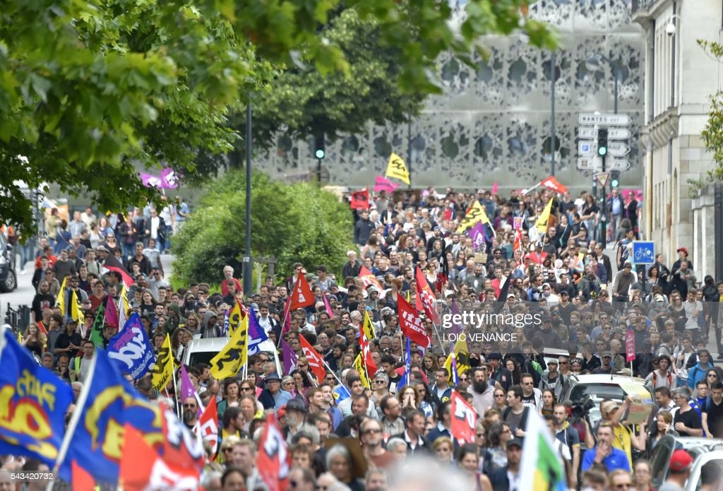 People take part in a demonstration against controversial labour reforms, on June 28, 2016 in Nantes, western France. People took to the streets in France on June 28 in the latest protest march in a marathon campaign against the French Socialist government's job market reforms. Last month the government used a constitutional manoeuvre to push the bill through the lower house without a vote in the face of opposition from Socialist backbenchers. / AFP / LOIC