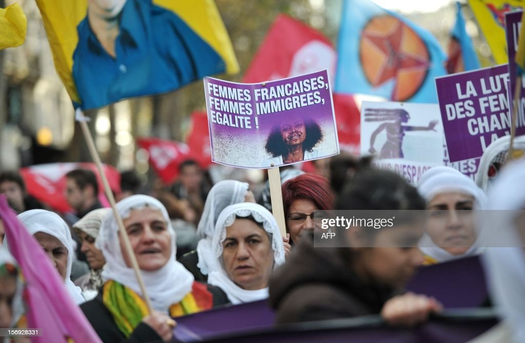 people take part in a demonstration called by the Women rights national collective, on November 25, 2012 in Paris, as part of the International Day for the Elimination of Violence Against Women. Since 1999, the United Nations each year invites governments, international organizations and NGOs to organize activities designed to encourage the public to fight such violence. Banner in the background reads: 'On November 25, support the fight against violence towards women.'.
