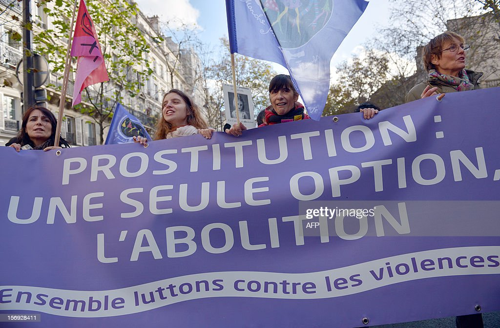 people take part in a demonstration called by the Women rights national collective, on November 25, 2012 in Paris, as part of the International Day for the Elimination of Violence Against Women. Since 1999, the United Nations each year invites governments, international organizations and NGOs to organize activities designed to encourage the public to fight such violence. Banner reads: 'Prostititution : only one solution, abolition'. AFP PHOTO BERTRAND LANGLOIS