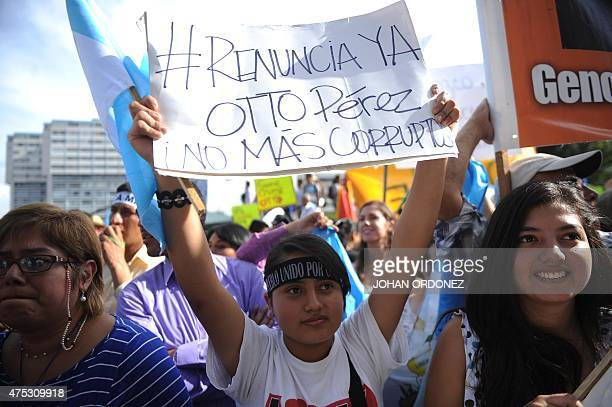 People take part in a demonstration demanding that Guatemalan President Otto Perez step down due to a corruption scandal that has shaken his...