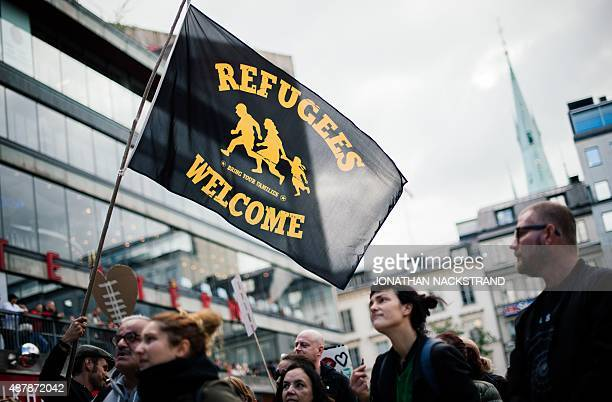 People take part in a demonstration in solidarity with migrants seeking asylum in Europe after fleeing their home countries in Stockholm on September...