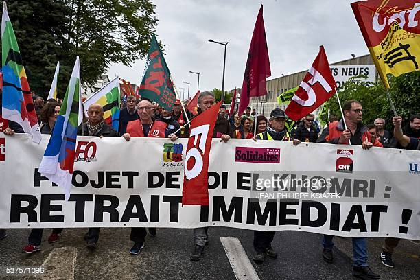 People take part in a demonstration of thousands of protesters against the government's planned labour law reforms during the visit of the French...