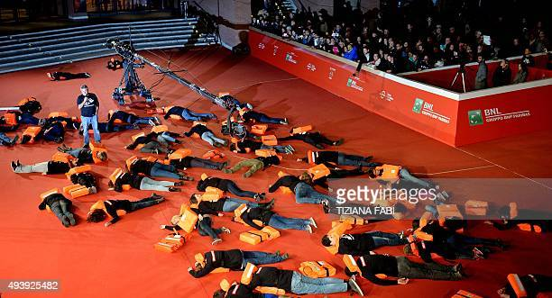 People take part in a Doctors Without Borders flash mob to highlight the tragedy of immigrants on the red carpet of the Rome Film Festival on October...