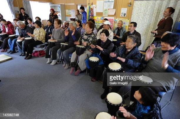 People take part in a drumming session on March 28 2012 in Miyagi Japan South Africans Bafana Mahlangu and Ronnie Medupi of Drum Cafe provided djembe...