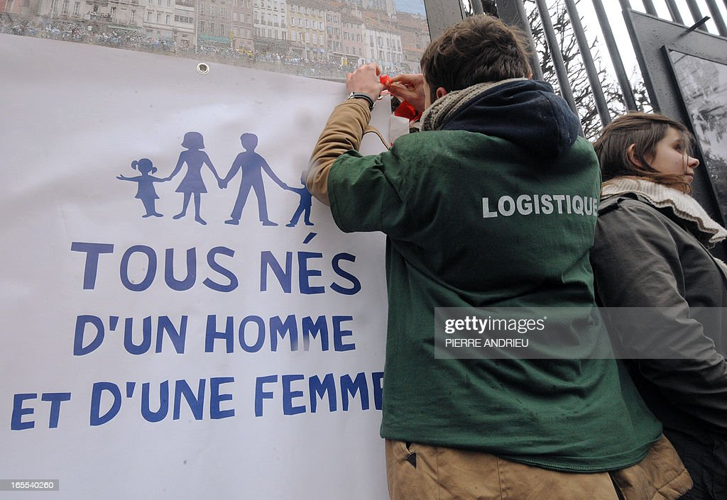 People take part in a protest against gay marriage on April 4, 2013 near the French Senate in Paris, on the first day of the debate at France's upper house on the controversial bill to legalise same-sex marriage and adoption. While the upper house is unlikely to reject the groundbreaking reform, it is still expected to be a tight vote as the ruling Socialists enjoy a smaller majority in the Senate than in the National Assembly. Banner reads 'All born from a man and a woman'.